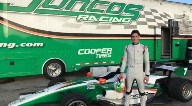 Alfonso Celis Jr. standing in front of his #7 car in front of the Juncos Racing trailer.